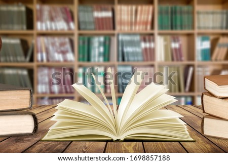 Old open book on library desk #1698857188
