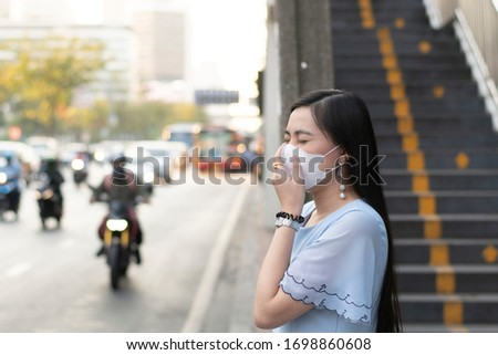 Asian woman is wearing protective mask to protect Covid-19 virus in Bangkok. #1698860608