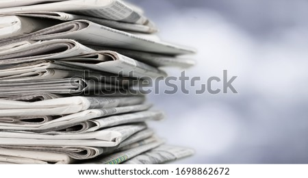 Pile of newspapers on blur background Royalty-Free Stock Photo #1698862672