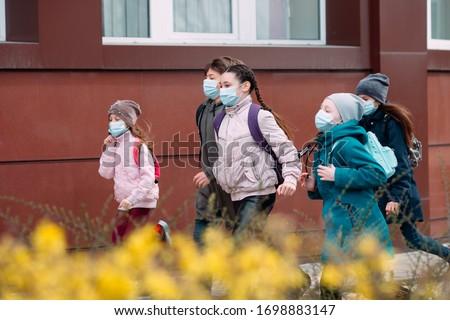 Children students in medical masks leave the school #1698883147