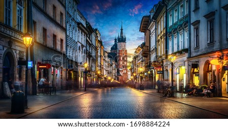 Evening view of St. Mary's Basilica from the Florianska street, old town Krakow, Poland. Panoramic view, long exposure, timelapse.   Royalty-Free Stock Photo #1698884224