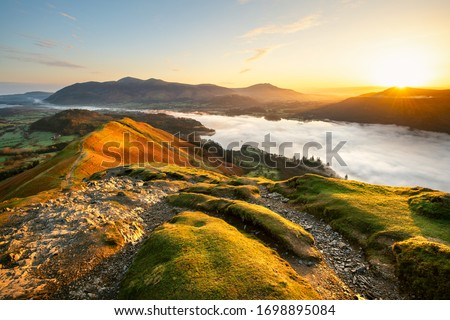 Beautiful Sunrise Overlooking Derwentwater From Catbells On A Sunny Calm Morning With Cloud Inversion Mist Over Lake. Lake District National Park, UK. Royalty-Free Stock Photo #1698895084