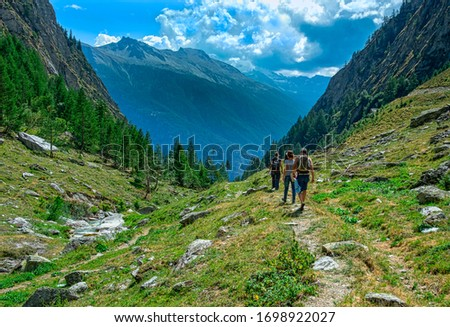 Walk in the Alps on a small way towards the valley #1698922027
