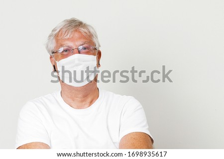 Old British men at risk by coronavirus. Old grey hair guy wearing a face mask for protection against coronavirus. Half body view of man wearing eye glass in paling white background with space for text #1698935617