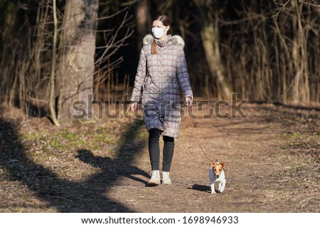 Young woman in warm jacket, wearing virus face mouth mask, walks her dog on country park road. Masks are mandatory  outside home during coronavirus covid-19 outbreak in some countries #1698946933