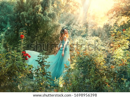 Fantasy princess enjoys summer nature. Vintage long dress flies fluttering in wind. Woman smile happy face. Spirituality divine light sun shine freedom concept, perfume aroma flowers natural cosmetics Royalty-Free Stock Photo #1698956398