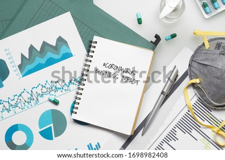 COVID-19 or Corona virus Business IMPACT background concept. Mockup Notebook for Covid 19 business impact anlysis with business graphs sheets, N95 facial masks and Alcohol Hand gel on office desk. Royalty-Free Stock Photo #1698982408