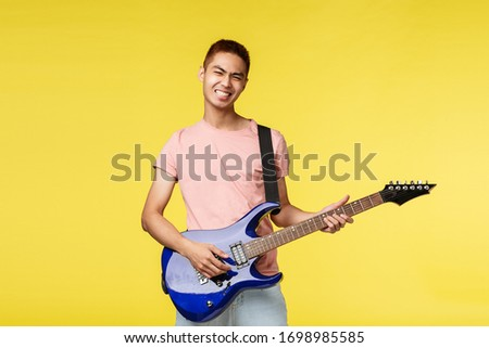 Lifestyle, leisure and youth concept. Lets jam. Carefree smiling asian guy playing in band, holding blue electric guitar, feel rock-n-roll start on stage, standing upbeat yellow background #1698985585