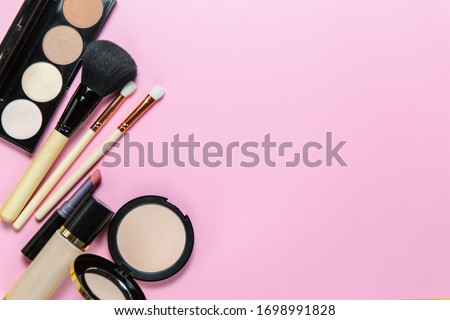 Makeup brushes, powder, eyeshadow palette, foundation for the face on a light pink background with place for text, top view Royalty-Free Stock Photo #1698991828