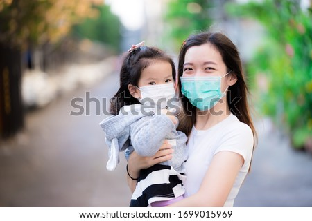 Asian family and adorable child girl wearing medical face masks on public roads. Mother and kid wear mask protection corona virus during outbreak pneumonia scourge. Face mask for protect pm2.5 dust. #1699015969