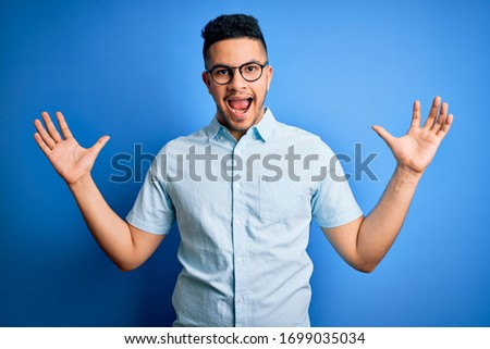 Young handsome man wearing casual summer shirt and glasses over isolated blue background celebrating crazy and amazed for success with arms raised and open eyes screaming excited. Winner concept #1699035034
