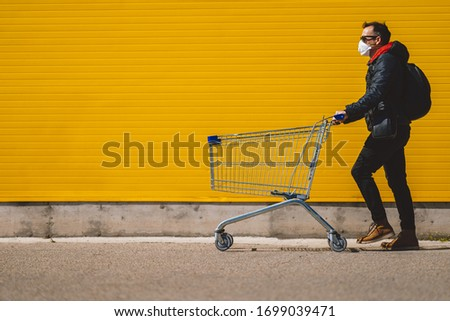 Man with with a shopping cart in front of a store, wearing a mask during a coronavirus pandemic / Covid-19. #1699039471
