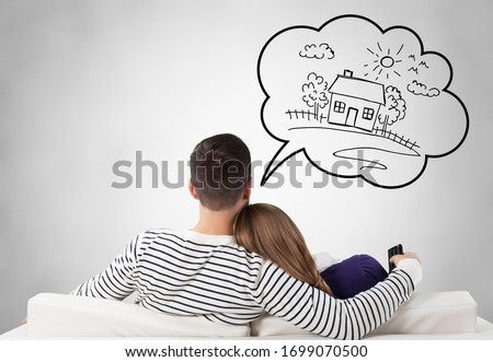 Young couple sitting on the sofa and thinking for house Royalty-Free Stock Photo #1699070500