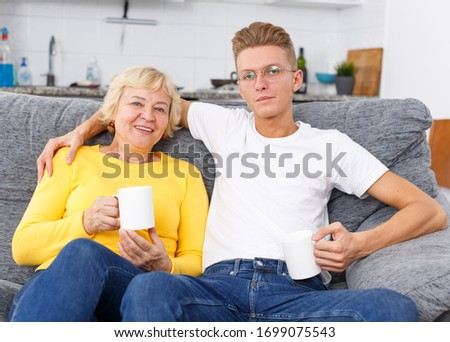 Portrait of loving mother and her adult son at kitchen #1699075543