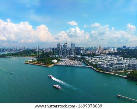 Panorama of the modern city-state of Singapore. Sunny weather, beautiful white clouds and blue sky. Skyscrapers, expensive yachts and the turquoise color of the sea. #1699078039