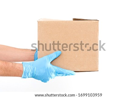 Delivery man holding cardboard boxes in medical rubber gloves and mask. copy space. Fast and free Delivery transport . Online shopping and Express delivery . Quarantine #1699103959