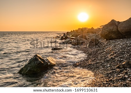 Orange sunset on the seashore with large stones. Large stones with beautiful texture on the background of dawn on the sea. Evening landscape rocky shore Royalty-Free Stock Photo #1699110631