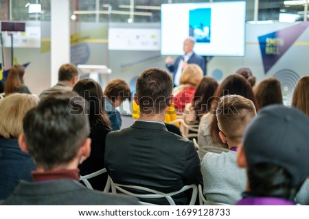 Audience listens lecturer at workshop in conference hall Royalty-Free Stock Photo #1699128733