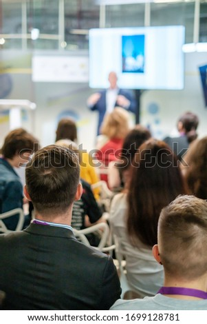 Audience listens lecturer at workshop in conference hall Royalty-Free Stock Photo #1699128781