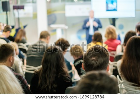 Audience listens lecturer at workshop in conference hall Royalty-Free Stock Photo #1699128784
