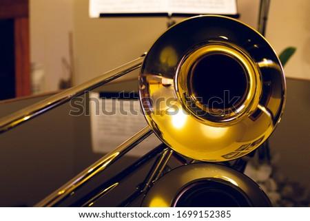 closeup of tenor trombone on the table Royalty-Free Stock Photo #1699152385