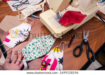 A stack of fabric cloth sewn masks with colorful patterns. People are making masks to cover the lack of PPE supplies for hospitals. Royalty-Free Stock Photo #1699158196