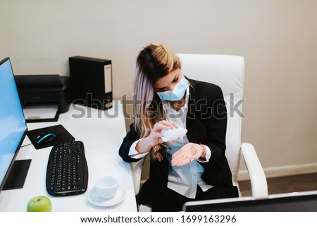 Young attractive caucasian businesswoman with mask pours hand sanitizer. COVID - 19 virus protection #1699163296