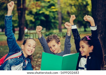 Happy little children celebrating success with raising hands. Three happy kids celebrating excellent results on a test at school. Selective focus Royalty-Free Stock Photo #1699202683