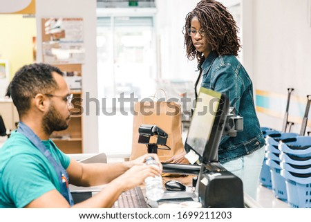 Side view of male cashier scanning goods at checkout. Young woman with buying groceries in supermarket. Shopping concept #1699211203