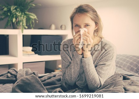 Sick young Caucasian woman covered with grey blanket sitting on bed, looking at camera, blowing nose with napkin. Illness, pain concept #1699219081