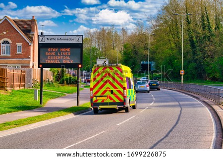 Traffic information sign in England during Covid 19 pandemic with  passing by blurry ambulance