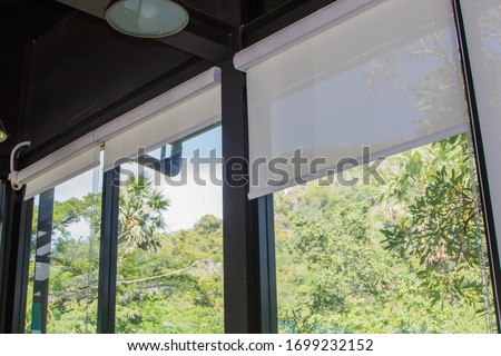 white roller blinds or curtains at the glass window #1699232152