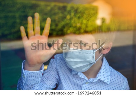Young ill boy looking sad with protective mask at home behind window in quarantine and lockdown missing school and freedom during Covid-19 Coronavirus worldwide pandemic  #1699246051