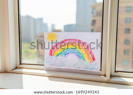 Kid with painted rainbow during Covid-19 quarantine at home. Caucasian Girl with teddy bear toy near window. Stay at home Social media campaign for coronavirus prevention, let's all be well