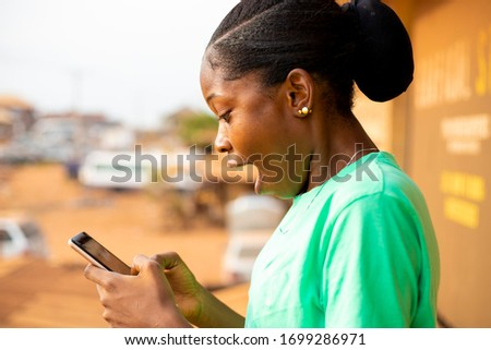young black African girl using mobile phone outdoor chatting with friends online Royalty-Free Stock Photo #1699286971