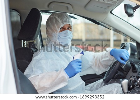 a man in a white protective medical suit with blue gloves, a mask in a car driving with a temperature measuring device during a coronavirus pandemic. horizontal  #1699293352