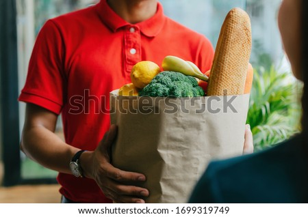 handsome food delivery service man in red shirt holding fresh food set bag to customer at door home, express delivery, quarantine, virus outbreak, takeaway food delivery and online shopping concept  #1699319749