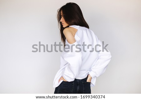 Beautiful girl dressed in white sweater with naked shoulder. Girl with long hair posing. She is dress in white hoodie. Sexy brunette look sensuality. Back view, turn around, looking over her shoulder. #1699340374