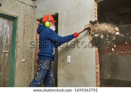 demolition work and rearrangement. worker with sledgehammer destroying wall #1699363792