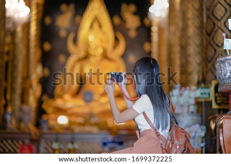Woman traveller pay gentle respect and taking photo picture on the buddha statue in the temple, praying respect for a better life forward