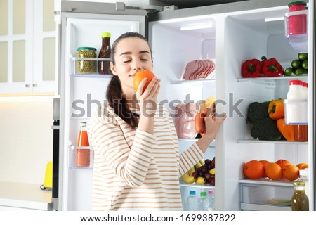 Young woman with orange near open refrigerator indoors #1699387822