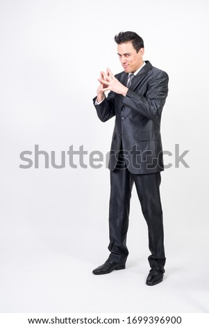 Evil man in suit machining a devilish plan. Full body, white background #1699396900