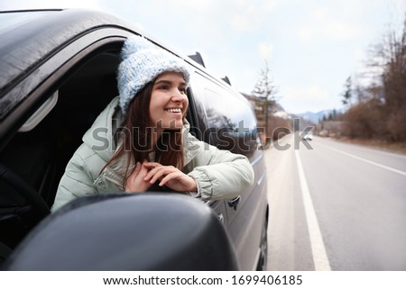 Happy woman leaning out of car window on road. Winter vacation