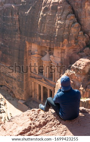 A traveller taking picture of the Treasury or Al Khazneh in Petra ruin and ancient city in Jordan, Asia #1699423255