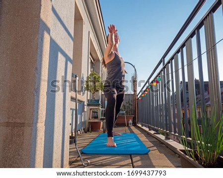 A woman practices yoga on the balcony of her apartment during the Covid-19 lock down in Geneva, Switzerland. The sun shines on the balcony as she maximizes the space available to work out from home. Royalty-Free Stock Photo #1699437793