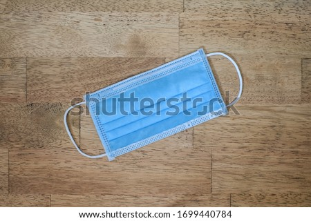 Surgical mask with rubber ear straps. Typical 3-ply surgical mask to cover the mouth and nose. prevention of the spread of virus and pandemic COVID-19 #1699440784