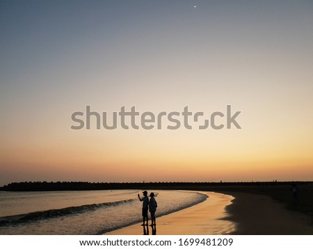 Sunset silhouette of young couple in love, taking photo and snuggling at beach. Reflection in a golden wet beach in evening, with new(crescent) moon and a star on a gradient sky. #1699481209