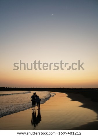 Sunset silhouette of young couple in love, taking photo and snuggling at beach. Reflection in a golden wet beach in evening, with new(crescent) moon and a star on a gradient sky. #1699481212