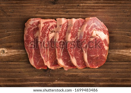 Raw fresh meat Ribeye steak entrecote and seasonings on cutting board #1699483486