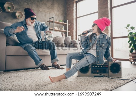 Photo of two people grandpa fan listen little granddaughter sing mic old fashion song cool style specs denim outfit hat house party sit tape player recorder stay home quarantine indoors